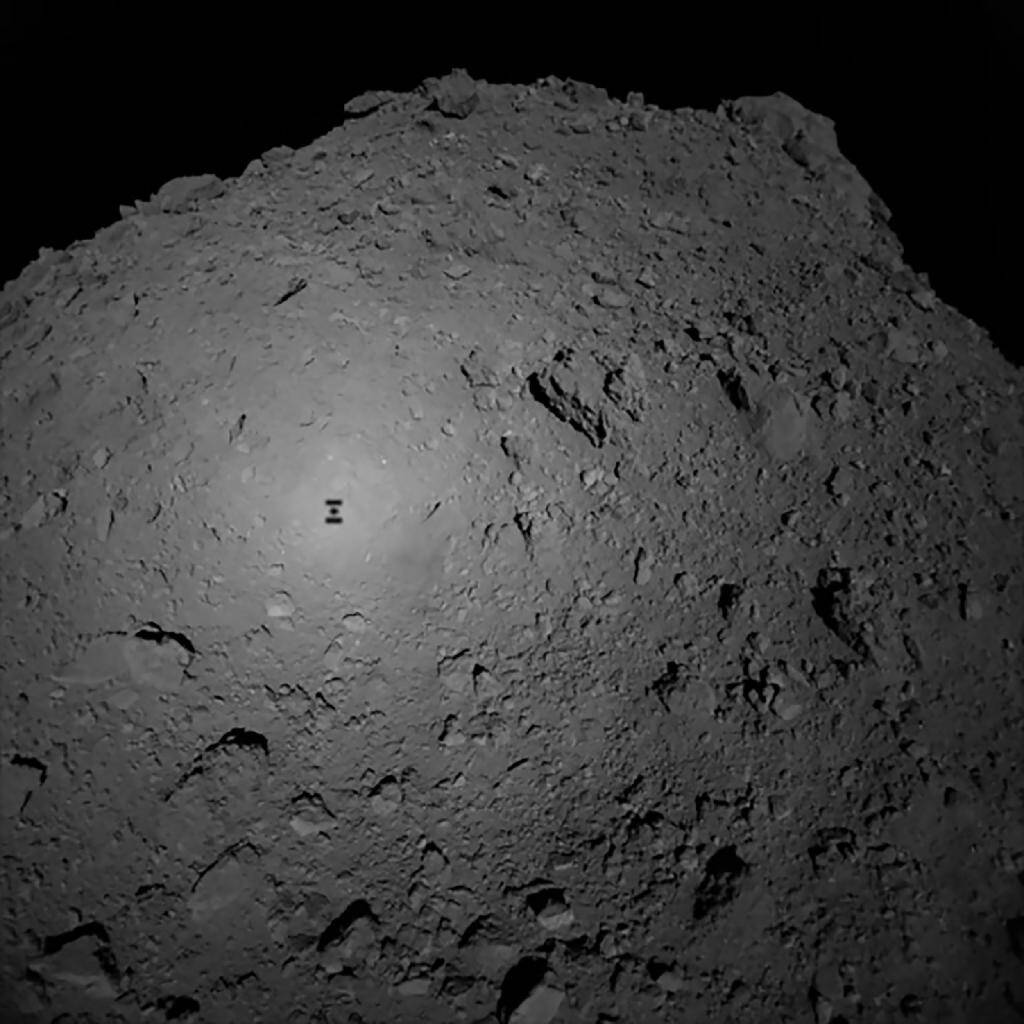 L'ombre de la sonde Hayabusa2 se porte sur l'astéroïde Ryugu, autour duquel elle tourne, le 3 octobre 2018.