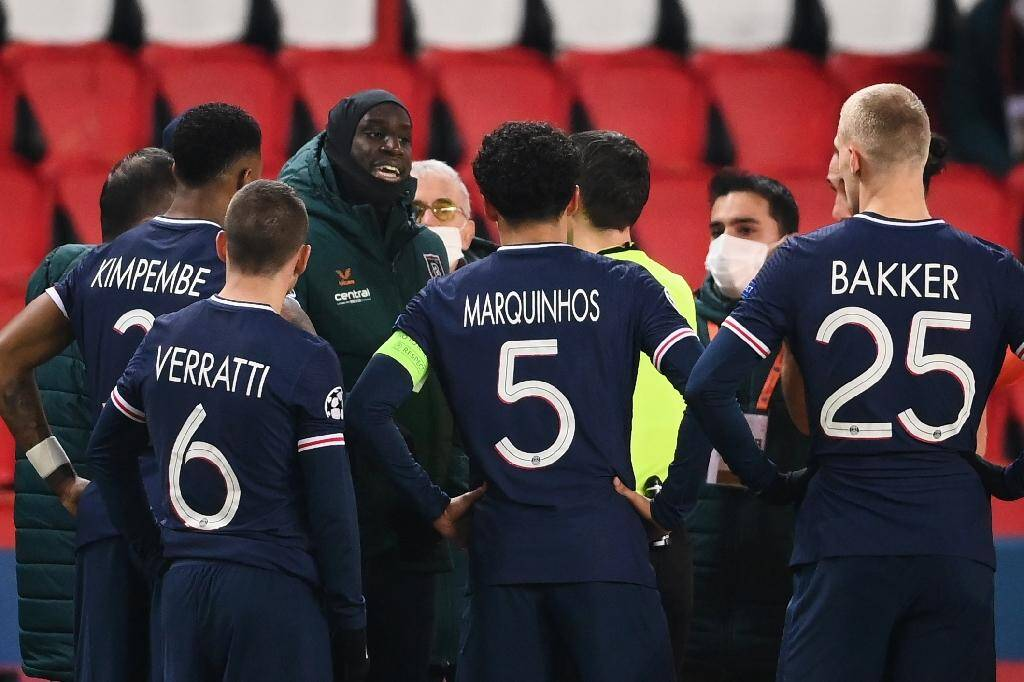 L'attaquant français de l'Istanbul Basaksehir, Demba Ba (g), s'adresse à l'arbire après l'interruption du match de groupes de la Ligue des champions contre le Paris-SG, au Parc des Princes, le 8 décembre 2020