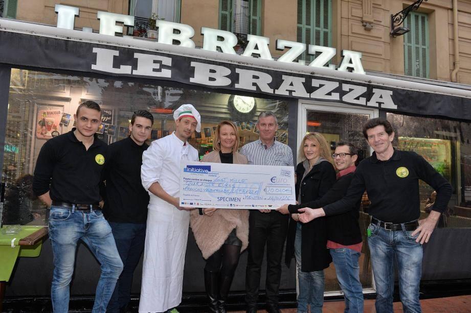 Marilyne Thomas et François Van der Linde (au centre) ont reçu de Sandra Paire, vice-présidente de Menton Initiative Riviera une aide de 20 040 euros pour aménager un coin pizzeria dans leur établissement « Le Brazza ».