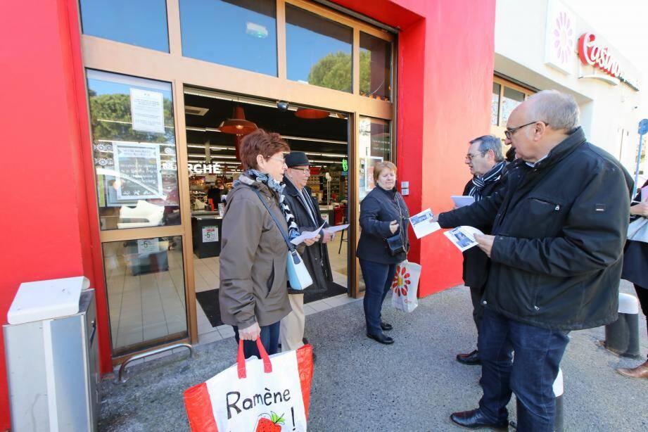 Devant le magasin, le maire et son adjoint à la qualité de vie distribuent des tracts.