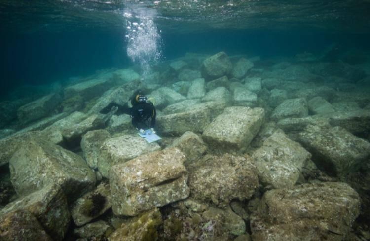 Prises de relevés sous-marins au milieu de blocs imposants de pierre qui devaient constituer une jetée, un quai ou un port.