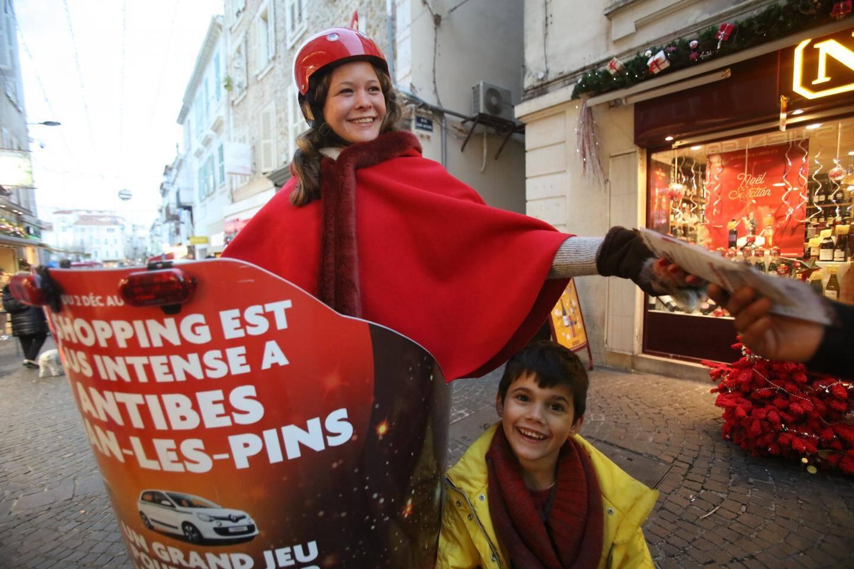 Hôtesses et sapins rouges devant les commerces.