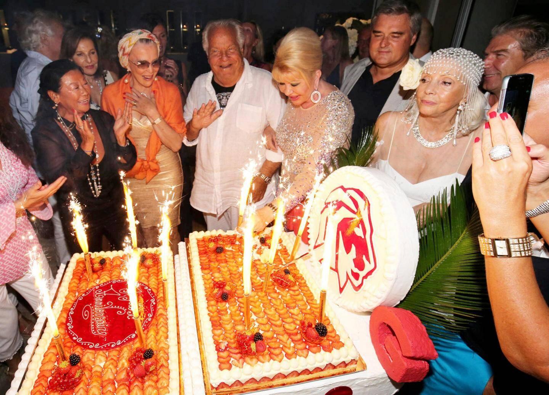 À minuit un fraisier géant inondé de fusées fontaines et frappé du signe du Lion est apparu sur le dancefloor avant d'être partagé par Ivana Trump et la maire du VIIIe arrondissement de Paris Jeanne d'Hauteserre (LR, en noir à gauche).