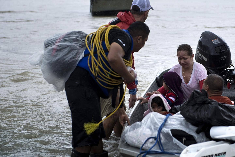 Des habitants arrivent en bateau après que leur quartier a été inondé.