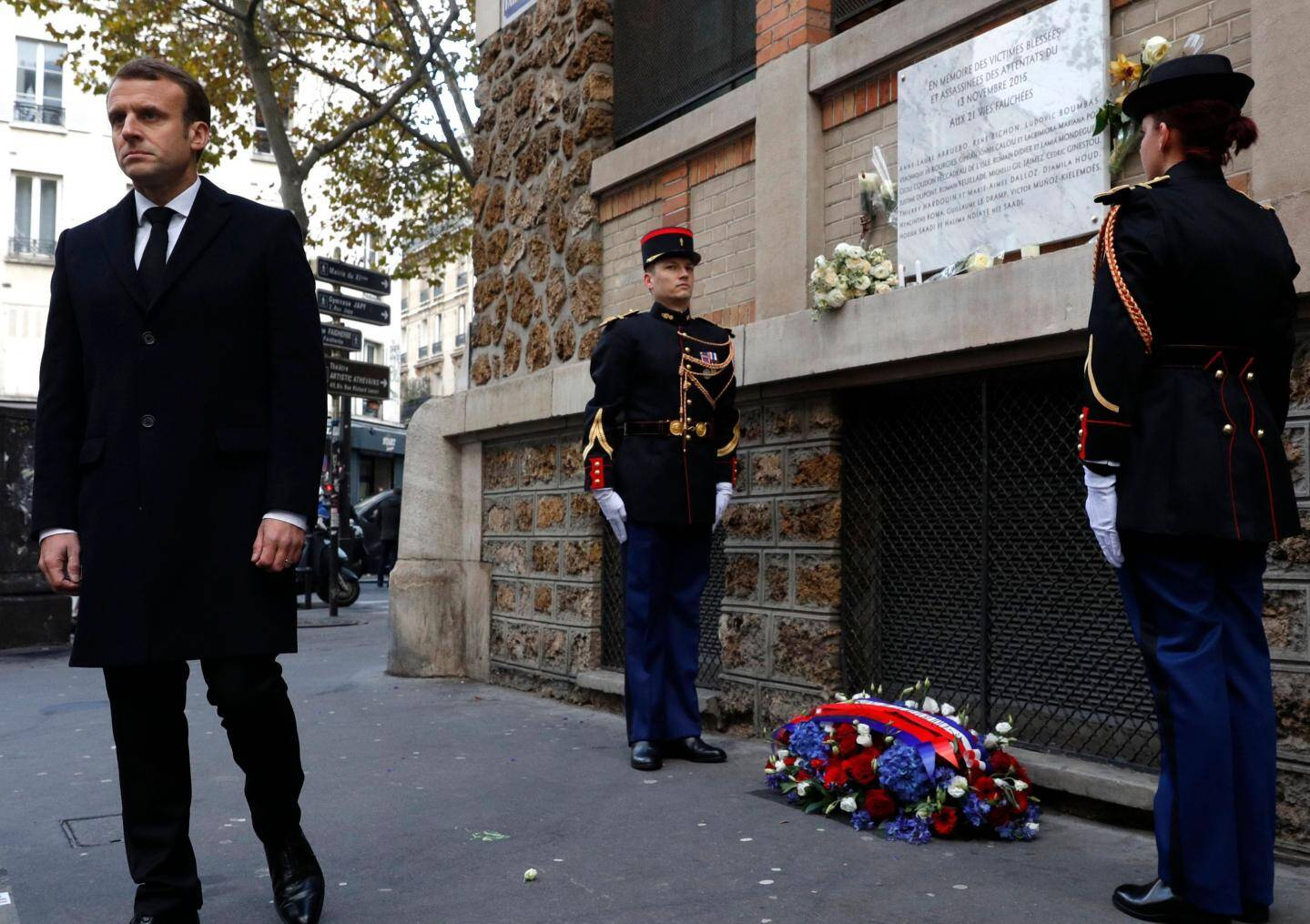French President Emmanuel Macron (L) looks on after laying a wreath of flowers in front of a commemorative plaque at