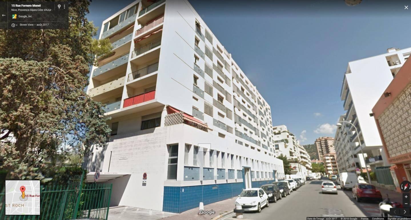 L'entrée du parking se situé à gauche de l'immeuble bleu et blanc.