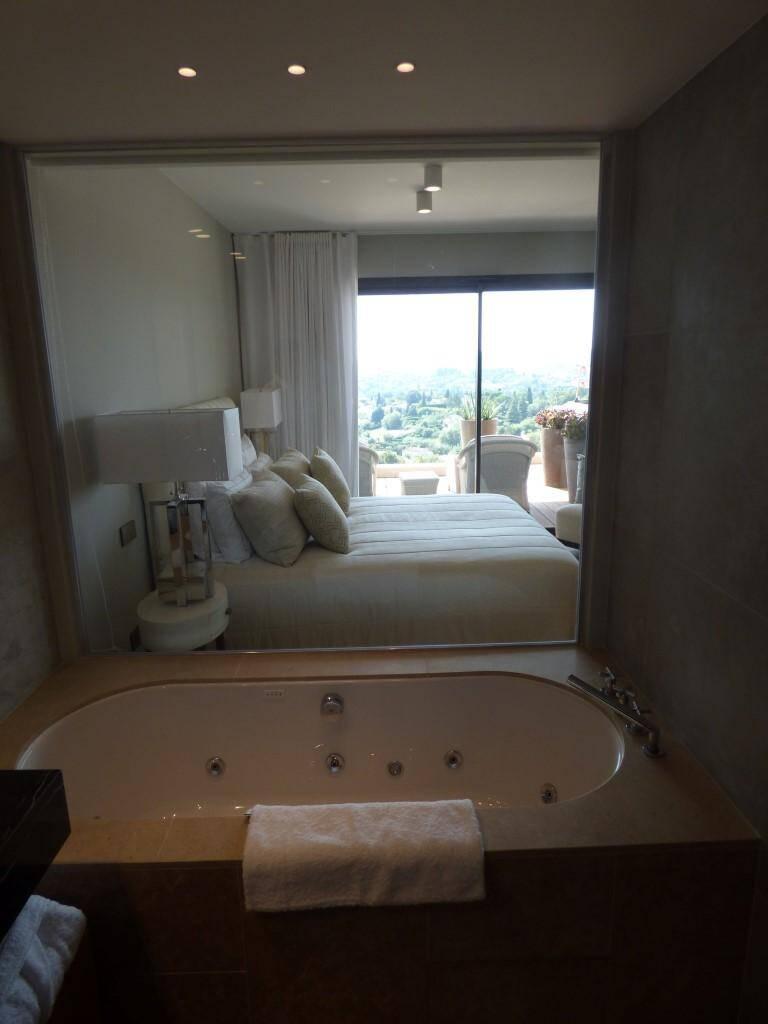 Le paysage depuis la salle de bains à travers la chambre et le balcon-terrasse.
