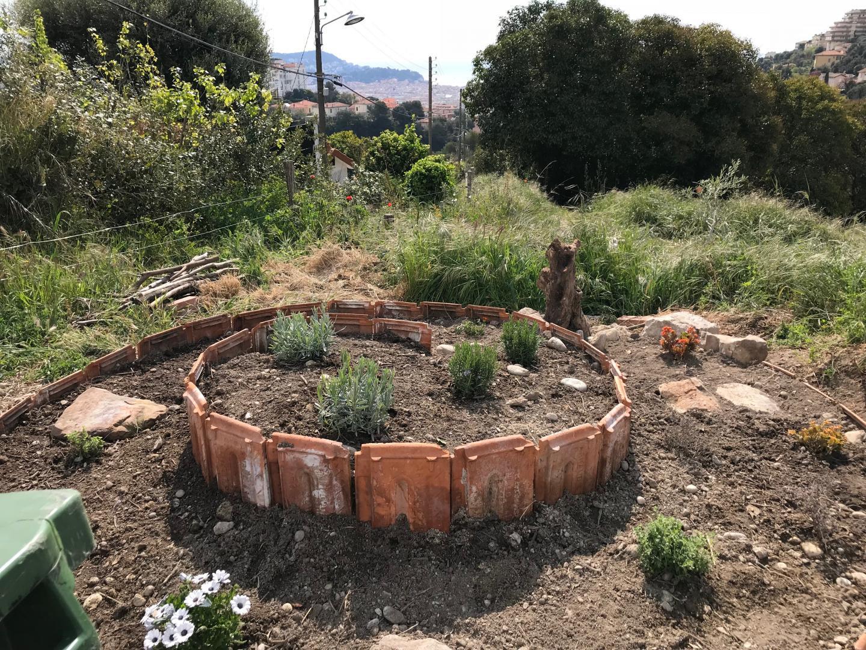 Une spirale d'herbes aromatiques surplombe le jardin.