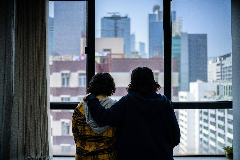Deux soeurs saoudiennes ayant fui à l'étranger regardent par une fenêtre à Hong Kong, le 22 février 2019