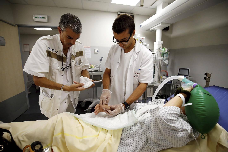 La patiente inhale du gaz Entonox pour ne pas sentir la douleur quand les médecins manipulent son pouce.