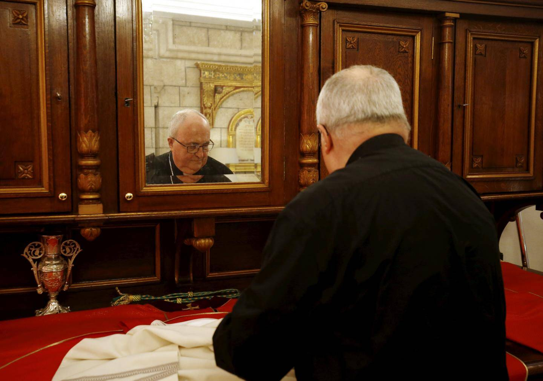 """9h40: l'heure de la messe approche. Mgr Barsi vérifie l'aube, la chasuble rouge et la croix épiscopale - tenue qui lui a été préparée par l'archidiacre Daniel Deltreuil pour sa """"dernière vraie messe""""."""