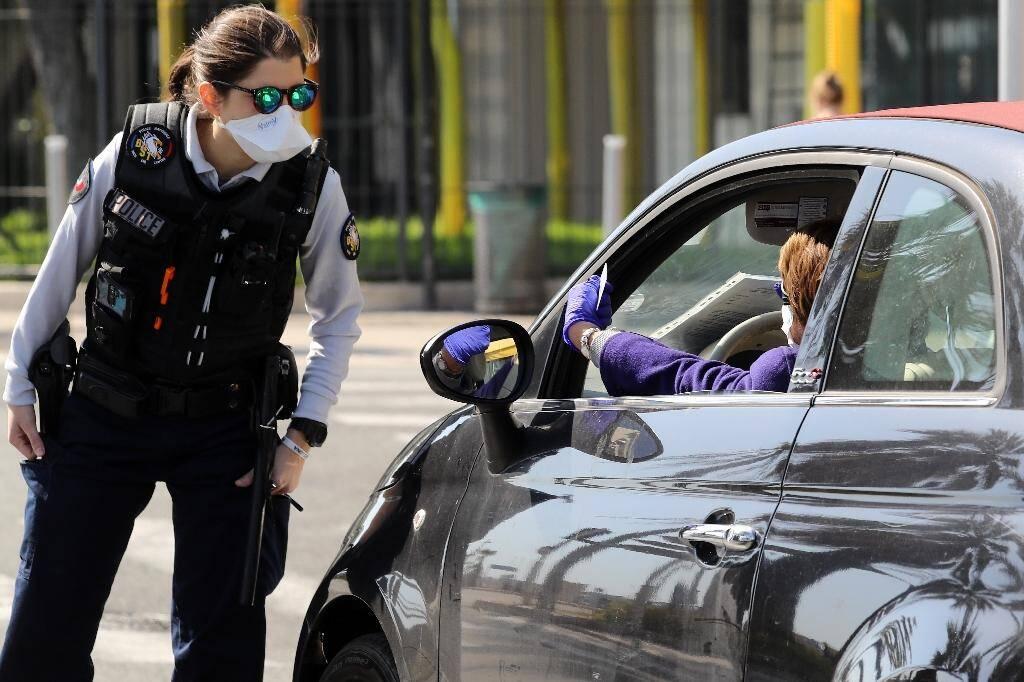 Une policière contrôle l'attestation dérogatoire de déplacement d'une automobilistes, le 6 avril 2020 à Nice