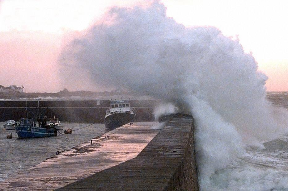 Une déferlante passe au-dessus de la jetée du port de Quiberon, le 03 janvier 2002