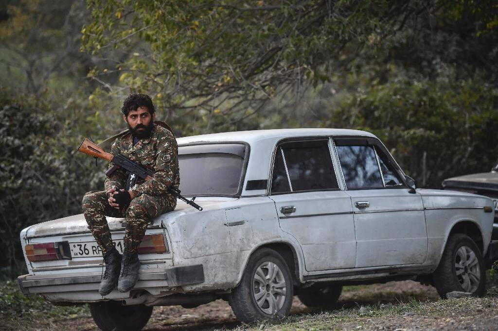 Un volontaire assis sur une voiture dans un village au sud-ouest de Stepanakert, le 23 octobre 2020