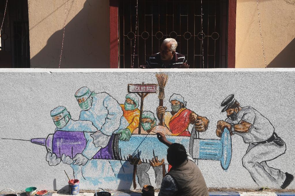 Des artistes terminent une peinture murale représentant des soignants portant le vaccin contre le virus à Kolkata le 2 janvier 2021