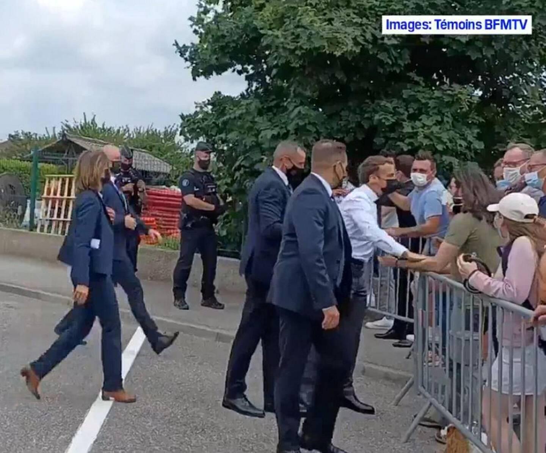 """Capture d'écran de la vidéo sur laquelle on voit Emmanuel Macron aller à la rencontre du public, avant de se faire gifler par Damien T. (t-shirt kaki). Le suspect a été arrêté, ainsi qu'un """"complice"""" qui avait filmé la scène."""