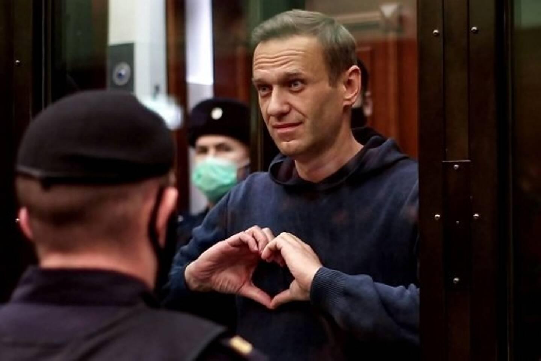 Cette photo, fournie par le service de presse du tribunal de la ville de Moscou, montre le chef de l'opposition russe Alexeï Navalny, accusé d'avoir violé les termes d'une condamnation avec sursis en 2014 pour détournement de fonds, faisant des gestes en forme de cœur depuis l'intérieur d'une cellule de verre lors d'une audience.