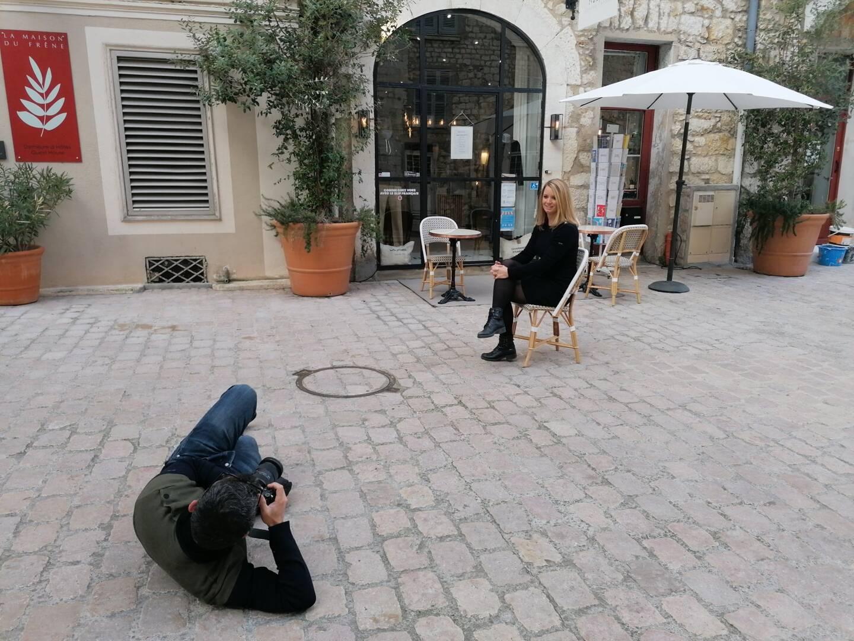 Franck Fernandes en train de photographier Amélie Serri, jeune commerçante à Vence, devant son concept store L'Atelier français.
