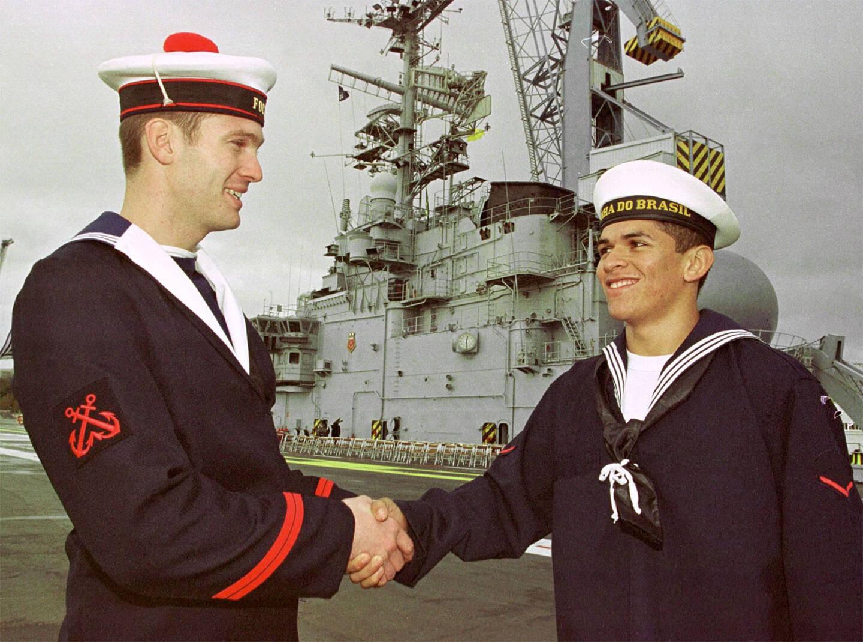 Alors que Foch est officiellement remis à la Marine brésilienne le 15 novembre 2000, un matelot français salue un matelot brésilien sur le nouveau São Paulo.