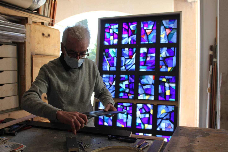 Jean-Pierre Bellion et le vitrail en cours d'élaboration dans son atelier de Castillon.