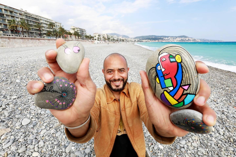 Hicham Chikhi peint des galets et les dissémine sur la plage de la promenade des Anglais.