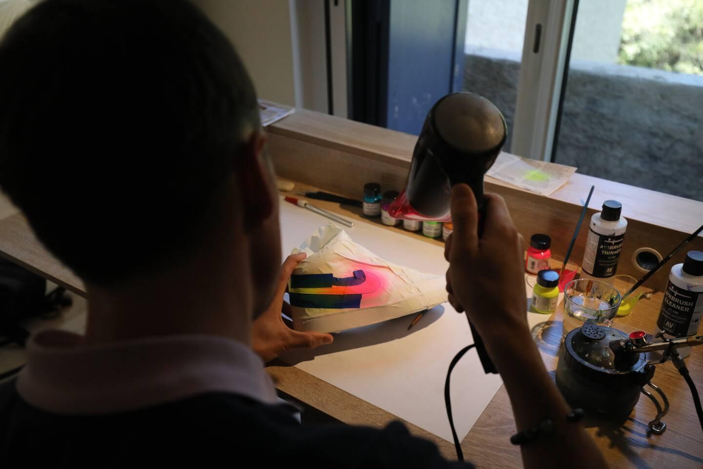 Aérographe, sèche-cheveux, peintures adaptées, pinceaux: dans son atelier, tout est à portée de main.