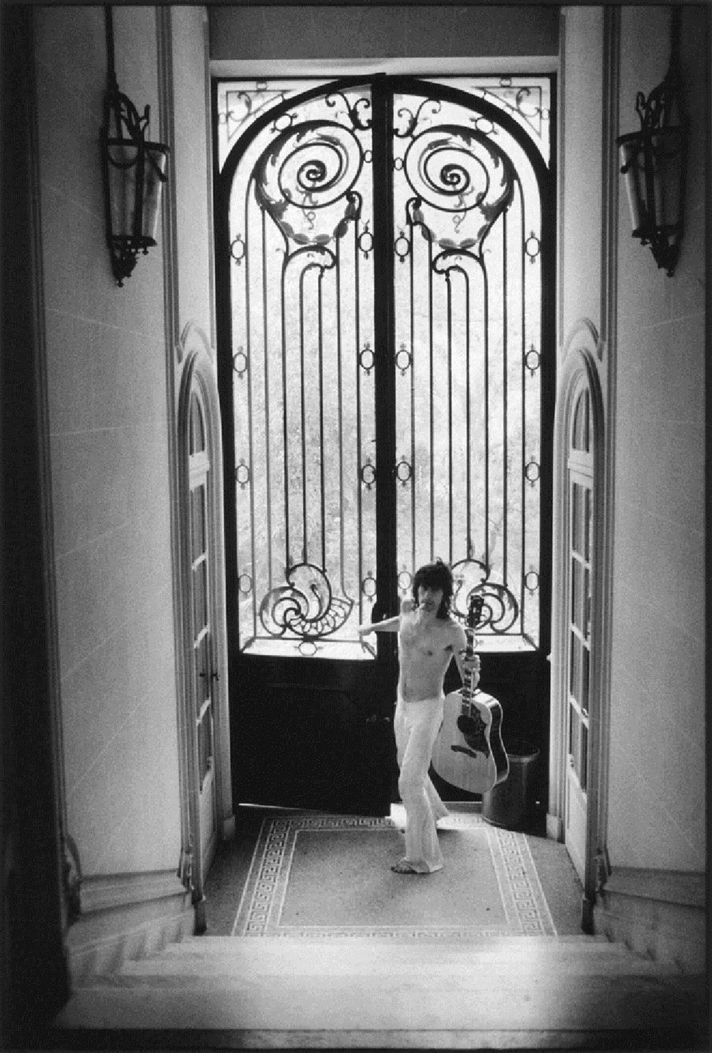 Keith Richards entrant dans la villa avec sa guitare qu'il ne quitte jamais.