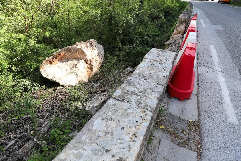 Dans sa chute, ce bloc de la taille d'une voiture a traversé l'axe routier, détruit une sculpture et le muret.