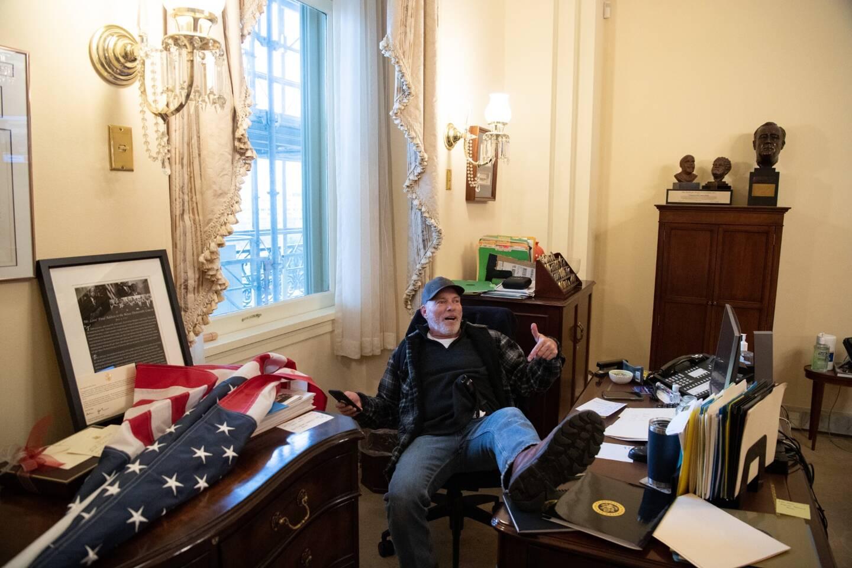 Richard Barnett, un supporter du président Donald Trump assis dans le bureau de Nancy Peolis, speaker démocrate de la Chambre des représentants lors de l'invasion du Congrès.