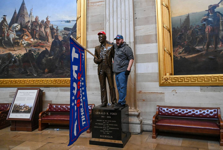 Un supporter du président Trump, dans le Capitole, sur la statue de Gerald Ford, ancien président des Etats-Unis.